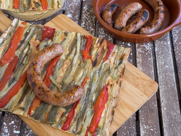 Ein stück coca de recapte eine typisch katalanische pizzaähnliche herzhafte pastete mit gegrillten auberginen und rotem pfeffer und schweinewurst auf einem rustikalen holztisch konzept der spanischen küche cuisine