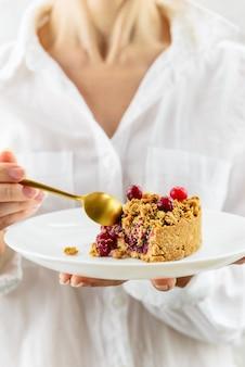Ein stück cranberry pie in einem weißen teller in den händen einer frau