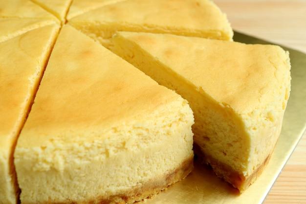Ein stück cremig gelber, normal gebackener käsekuchen, der aus dem ganzen kuchen geschnitten wurde
