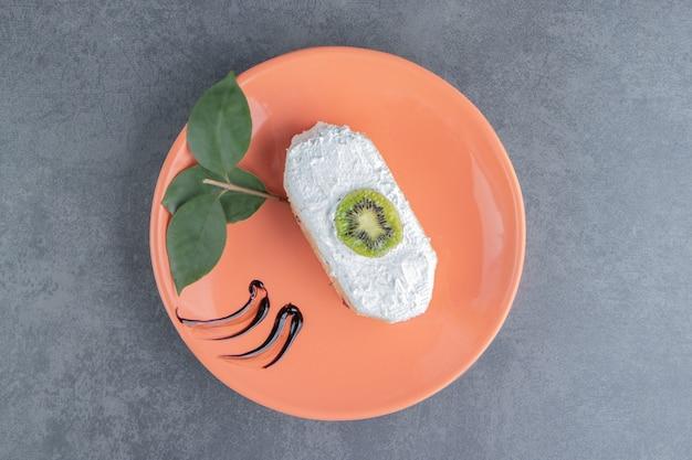 Ein stück cremiger kuchen mit einem stück kiwi und blättern