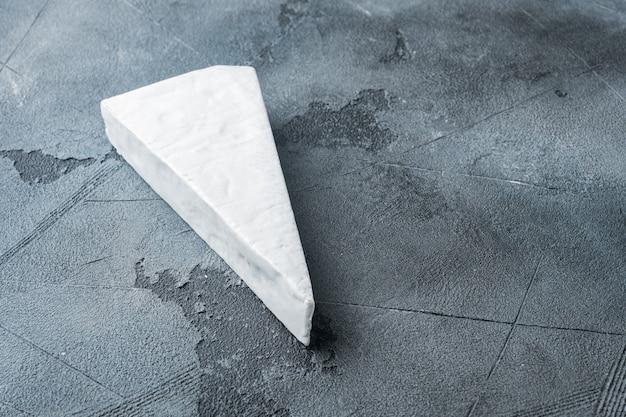 Ein stück cremiges weichkäseset des brie-bauernhauses auf grauem tisch
