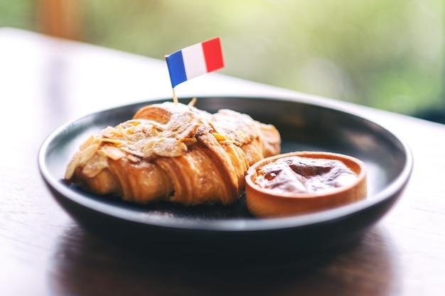Ein stück croissant und torte mit einer flagge von frankreich in einem schwarzen teller auf holztisch im café