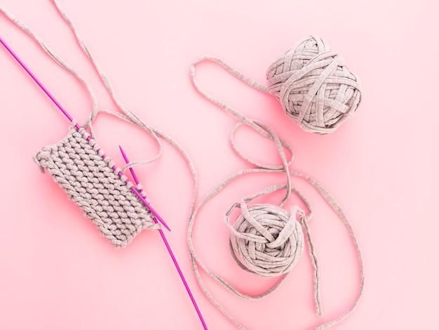Ein stück des strickens mit ball des grauen garns und der violetten stricknadeln auf rosa bacground.
