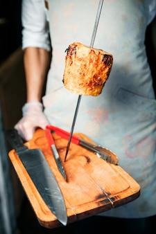 Ein stück, drapierte ananas, liegt am spieß. chefkoch hält einen koch in weißen handschuhen. der spieß ruht auf einem holzschneidebrett.