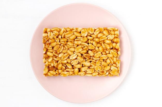 Ein stück erdnusskrokant auf dem teller. nahrungsmittelenergiemodell. hintergrundbild für süße snacks. draufsicht, flache lage, kopierraum.