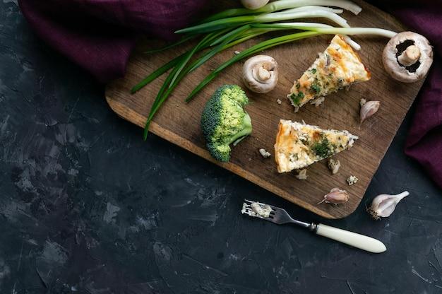 Ein stück fleischtorte mit brokkoli auf einem hölzernen brett, tischbestecklüge in der nähe, grauer hintergrund, draufsicht