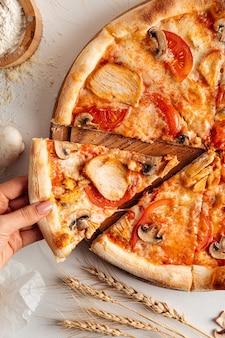 Ein stück frisch gebackene hühnerpizza nehmen