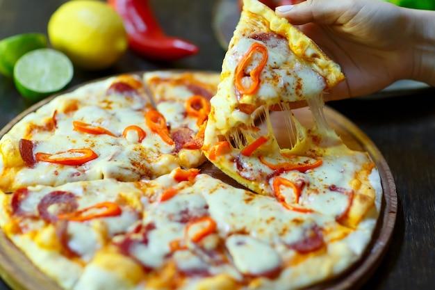 Ein stück frische heiße pizza mit einem stück mozzarella in der hand.