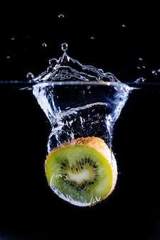 Ein stück frische kiwi spritzt mit einem schwarzen ins wasser