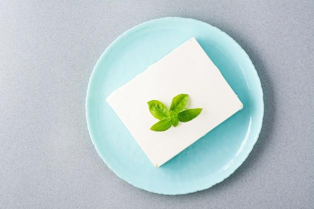 Ein stück frischer feta-käse und basilikumblätter auf einem teller auf dem tisch.