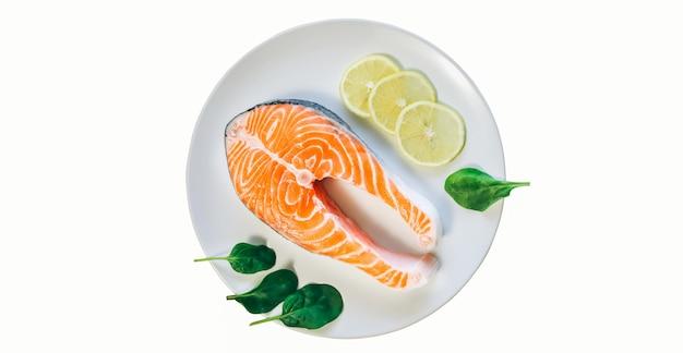 Ein stück frischer lachs auf weißem hintergrund. fischsteak auf einem weißen teller mit spinat und zitrone. omega-3-vitamin, gesunder lebensstil. natürliches vegetarisches essen. ansicht von oben.