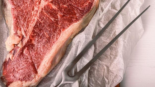 Ein stück frisches farmfleisch t-bon ohne gvo, eingewickelt in umweltfreundliches geschenkpapier
