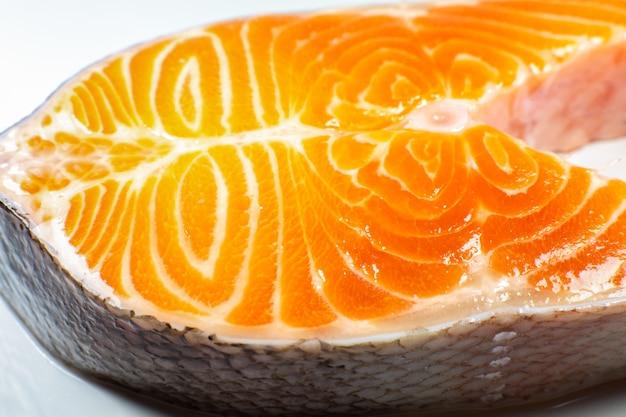 Ein stück frisches lachsfischsteak auf weißem hintergrund. omega-3-vitamin, gesunder lebensstil. natürliches vegetarisches essen. ansicht von oben. nahaufnahme foto.