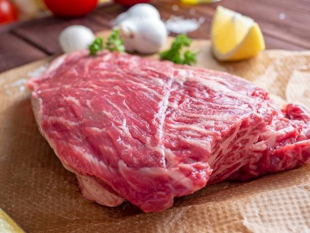 Ein stück frisches rohes rindfleisch liegt auf pergament umgeben von gewürzen, kräutern und gemüse. seitenansicht. lebensmittelzusammensetzung