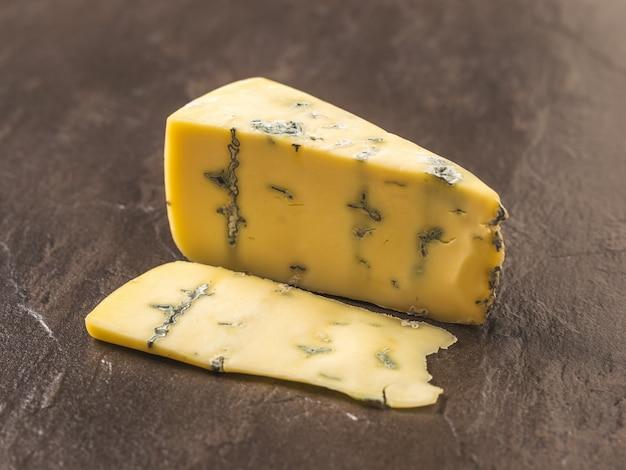 Ein stück frischkäse mit blauschimmel auf einem dunklen steintisch. käsespezialität. eine nützliche form