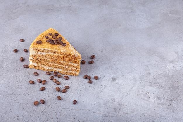 Ein stück geschichteten honigkuchens mit kaffeebohnen, die auf einen steinhintergrund gelegt werden.