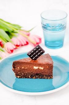 Ein stück gesunder schokoladen-brownie-rohkuchen mit haselnüssen, einem glas wasser und rosa tulpen