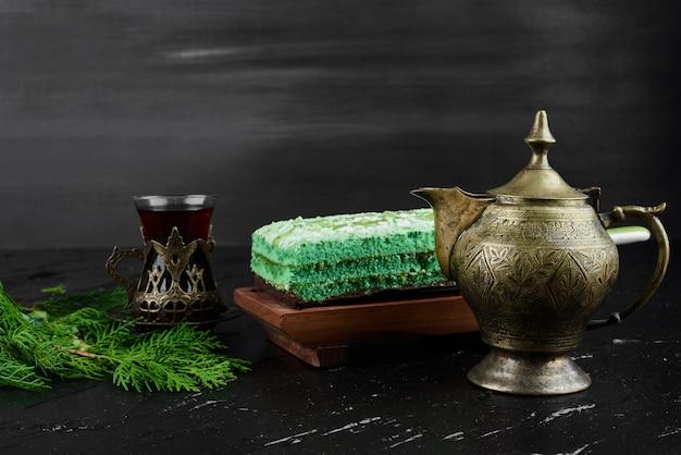 Ein stück grüner kuchen mit einem glas tee.