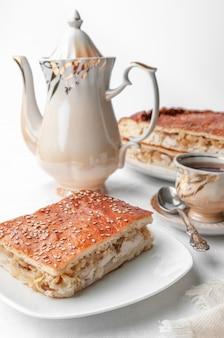 Ein stück hausgemachte hühnchen-sesam-torte. auf einem weißen teller. in der nähe einer kaffeekanne und einer tasse kaffee. weißer hintergrund.