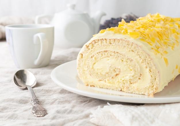 Ein stück hausgemachter biskuitkuchen mit banane, garniert mit schokolade auf einem weißen teller im hintergrund ist eine weiße teekanne und eine tasse closeup