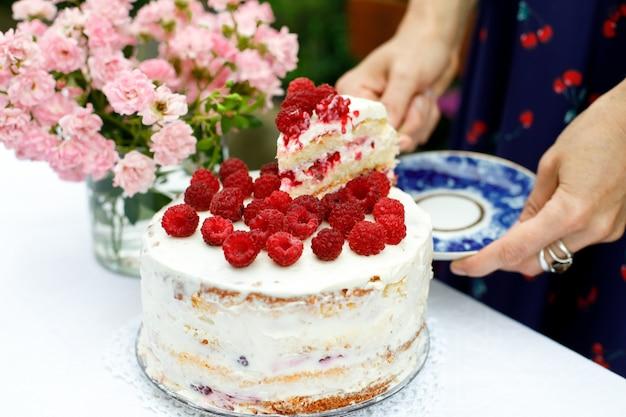 Ein stück hausgemachter himbeerkuchen auf einer untertasse in weiblichen händen neben einem kuchen im sommergarten. selektiver fokus