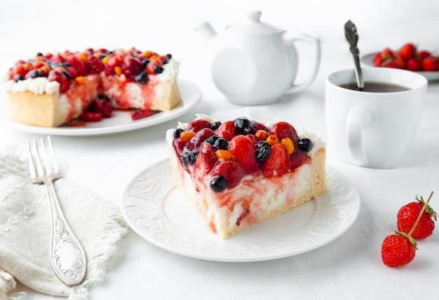 Ein stück hausgemachter hüttenkäse-beerenkuchen garniert mit sahne-erdbeeren heidelbeeren sanddornbeeren auf einem weißen teller neben dem teller ist eine gabel eine serviette erdbeeren