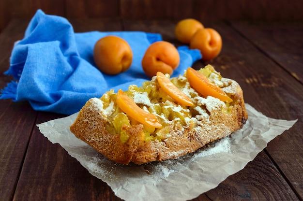 Ein stück hausgemachter kuchen mit apfelscheiben und aprikosen, dekorativer puderzucker.