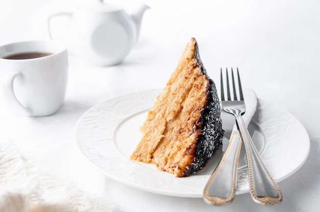 Ein stück hausgemachter mehrschichtiger kekskuchen in butter getränkt serviert mit schokoladenglasur und kokosnuss auf einem weißen teller ist eine gabel mit einem messer nahaufnahme
