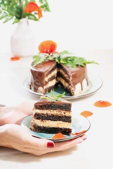 Ein stück hausgemachter schokoladenkuchen mit erdnussbutter-cremeschichten, verziert mit mohnblumen und blütenblättern in männlichen händen über einem weißen schreibtisch. selektiver fokus.
