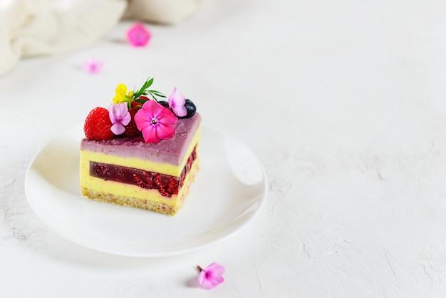 Ein stück himbeer-zitronen-mousse-kuchen auf einer hellen oberfläche. zucker-, laktose- und glutenfrei. horizontale ausrichtung, kopierraum.