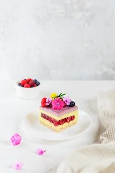 Ein stück himbeer-zitronen-mousse-kuchen mit himbeergelee auf einer hellen oberfläche. zucker-, laktose- und glutenfrei.
