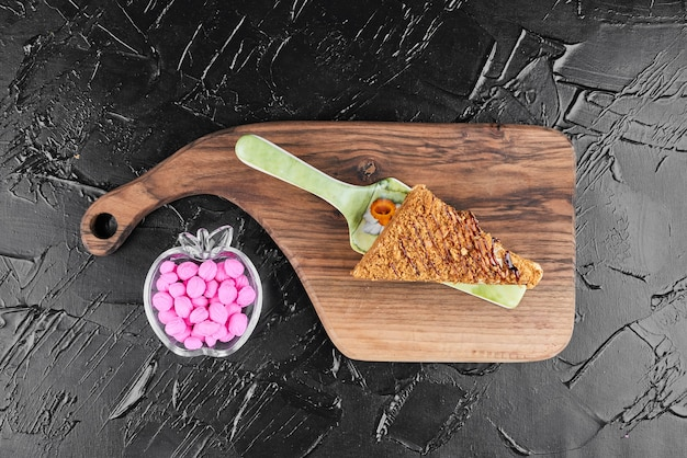 Ein stück honigkuchen mit rosa bonbons, draufsicht.