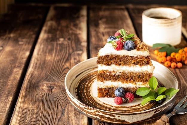 Ein stück karottenkuchen mit beeren und feigen auf einem holz verziert. traditionelles eselgebäck.