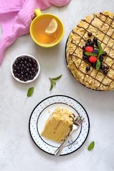 Ein stück köstliches festliches schichtdessert mit blätterteig und pudding und einer tasse zitronentee