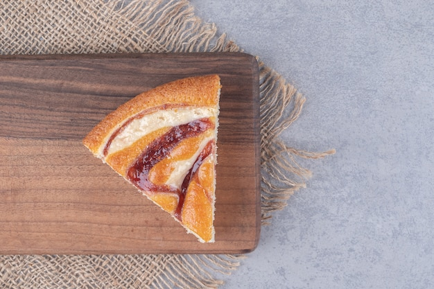 Ein stück kuchen auf einem holzbrett auf marmortisch.