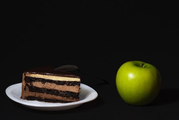 Ein stück kuchen auf einem weißen teller und ein reifer grüner apfel auf schwarzem hintergrund gesundes ernährungskonzept