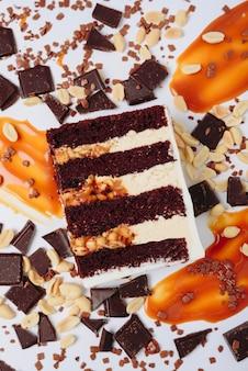 Ein stück kuchen in einem abschnitt auf einem hintergrund von schokolade und karamell