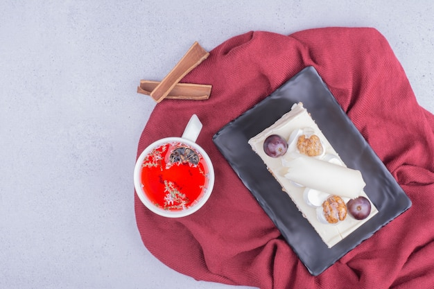Ein stück kuchen in einer keramikplatte mit einer tasse rotem kräutertee.