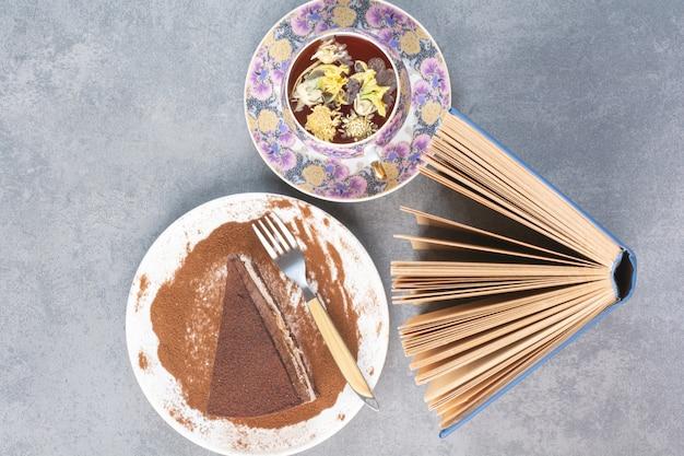 Ein stück kuchen mit aroma-tee und buch.