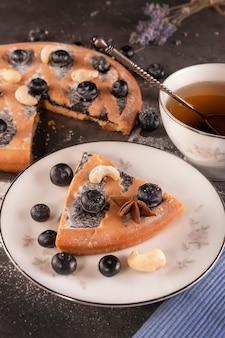 Ein stück kuchen mit blauen beeren auf einer untertasse und eine tasse tee mit einem silbernen löffel auf einem dunklen tisch