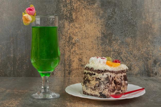 Ein stück kuchen mit einem glas saftiger grüner limonade auf marmorwand