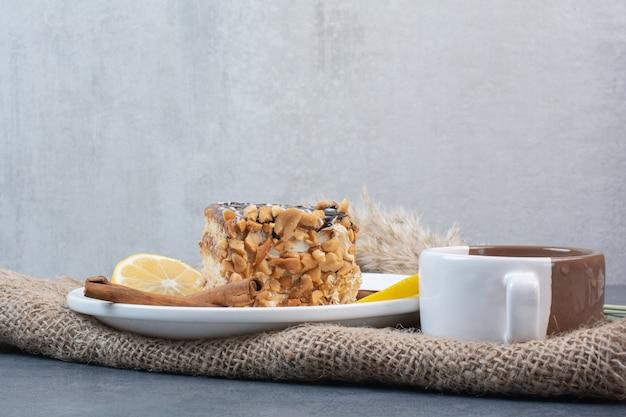 Ein stück kuchen mit einer tasse aromakaffee auf sackleinen.