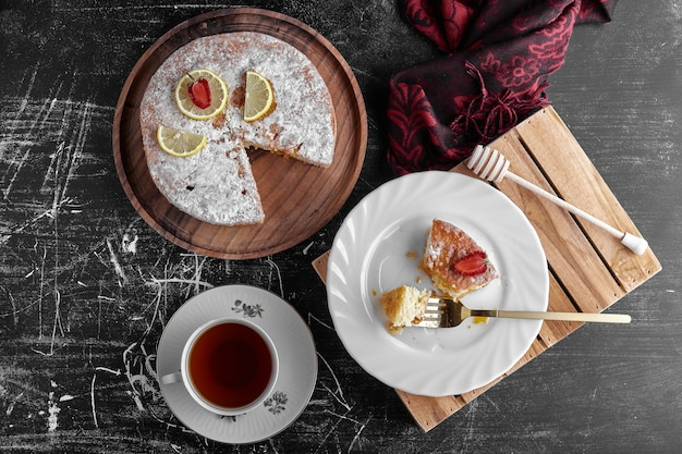 Ein stück kuchen mit einer tasse tee, draufsicht.