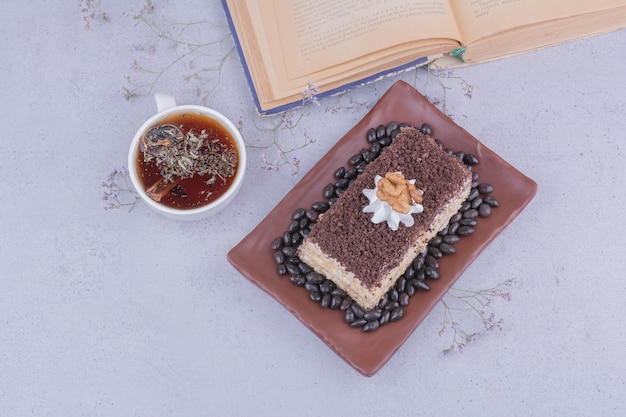 Ein stück kuchen mit gehackter schokolade und einer tasse kräutertee