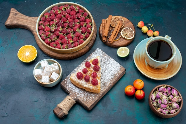 Ein stück kuchen mit halber draufsicht, süß gebacken mit himbeeren und tee auf einem dunklen schreibtisch mit beerenkuchen