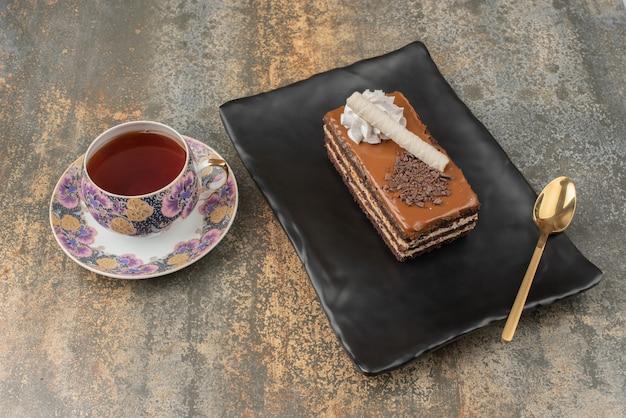 Ein stück kuchen mit heißem tee und löffel auf dunklem teller