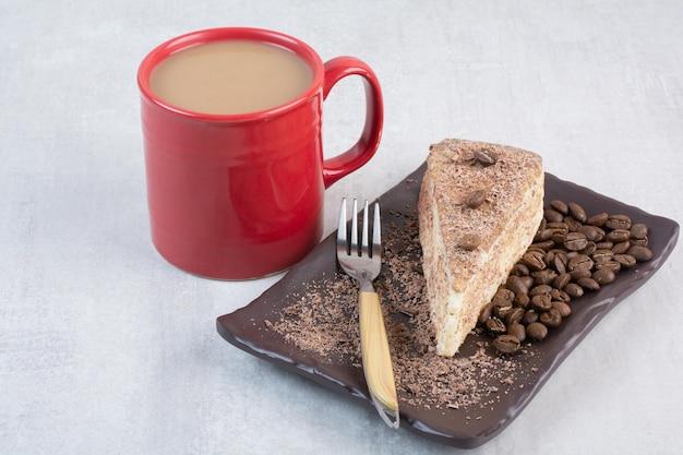 Ein stück kuchen mit kaffeebohnen und einer tasse kaffee