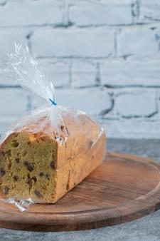 Ein stück kuchen mit plastikfolie umwickelt auf holzbrett.