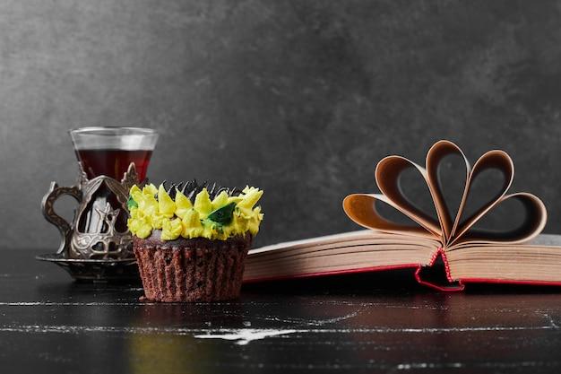 Ein stück kuchen mit sonnenblumencreme-dekoration, serviert mit einem glas tee.