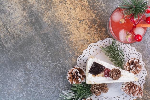 Ein stück kuchen mit tannenzapfen und kaltem erdbeersaft mit stroh
